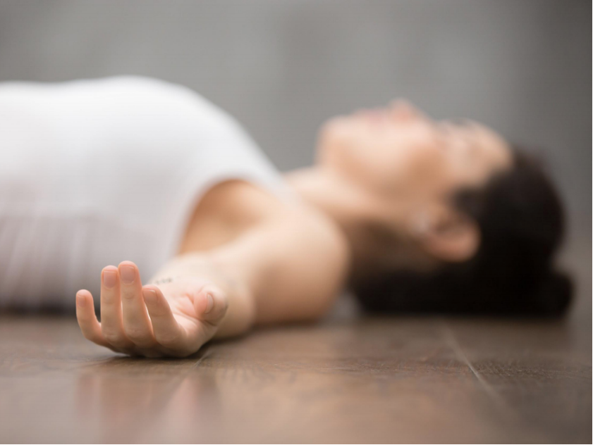 Picture of a woman laying in savasana